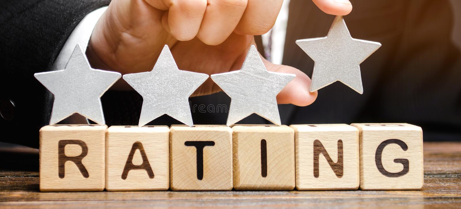 Businessman puts a fourth star above the word Rating on wooden blocks. The concept of the high rating of hotels and restaurants. The evaluation of critics and royalty free stock photos