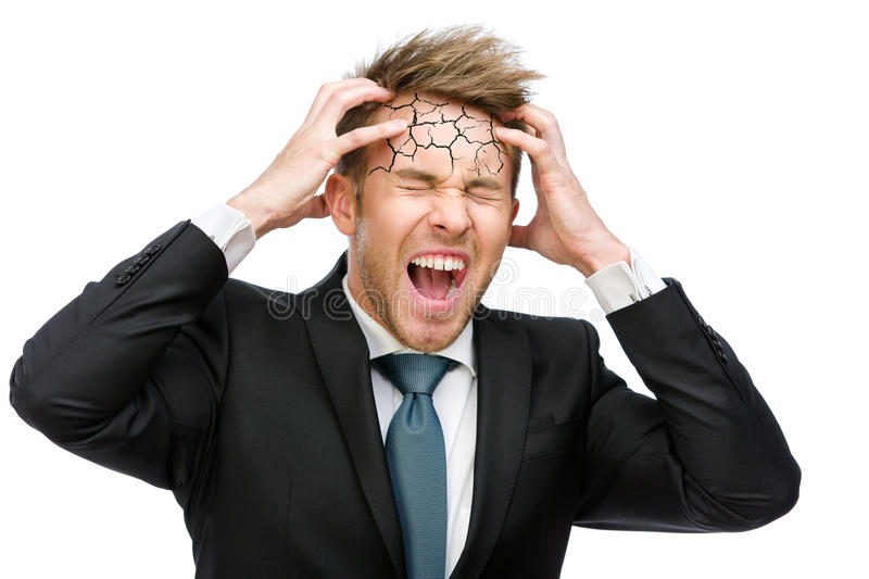 Businessman puts hands on cracked head and shouts royalty free stock photo
