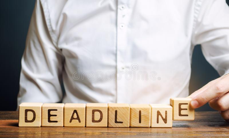 Businessman puts wooden block with the word Deadline. A narrow field of time by which an objective must be accomplished. Time royalty free stock images