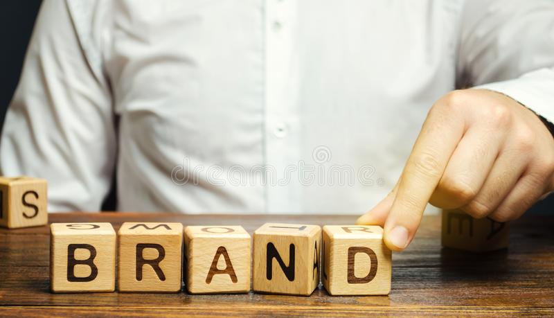 Businessman puts wooden blocks with the word Brand. Business, marketing, and advertising. Name, term, design, symbol that. Identifies one seller`s good or royalty free stock photo