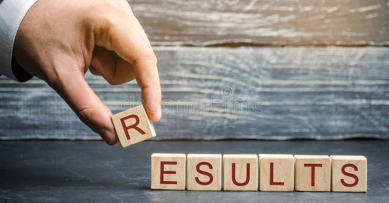 Businessman puts wooden blocks with the word Results. The concept of annual financial statements. Analysis of profits and revenues royalty free stock image