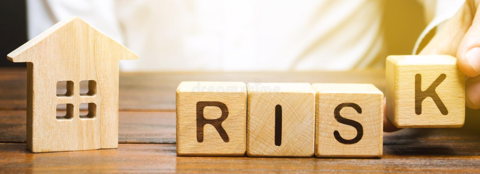 Businessman puts wooden blocks with the word Risk and a house. Real estate investment risk. Risky investments. Loss of property. For non-payment. Debts stock images