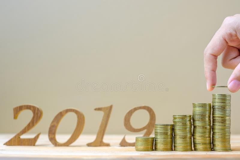 "Businessman putting and accounting money with ""2019"" number background, gold coins stack on wooden table. business, investment stock photo"