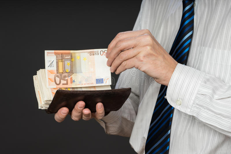 Businessman putting banknotes in his wallet. Stack of fifty euros money. Business man is holding cash. Person pays in euro bills. Isolated gray background royalty free stock images