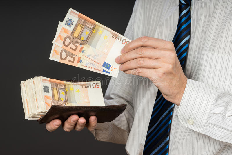 Businessman putting banknotes in his wallet. Stack of fifty euros money. Business man is holding cash. Person pays in euro bills. Isolated gray background royalty free stock photography
