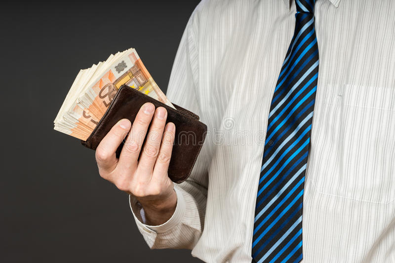 Businessman putting banknotes in his wallet. Stack of fifty euros money. Business man is holding cash. Person pays in euro bills. Isolated gray background royalty free stock photo