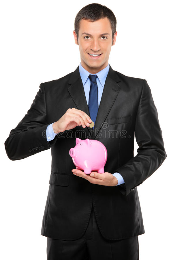 A businessman putting a coin into a piggy bank royalty free stock photography