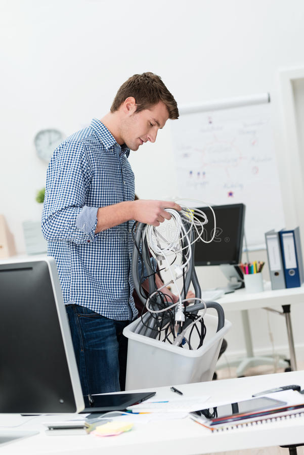 Businessman putting computer cables in a bin royalty free stock photos