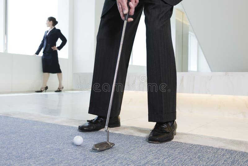 Businessman putting golf ball. stock photo