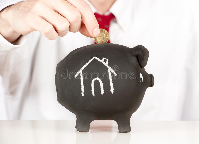 Businessman putting money on a piggy bank royalty free stock image
