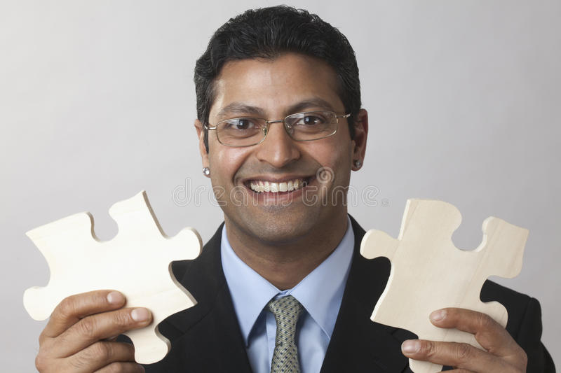 Businessman putting the puzzle together royalty free stock image