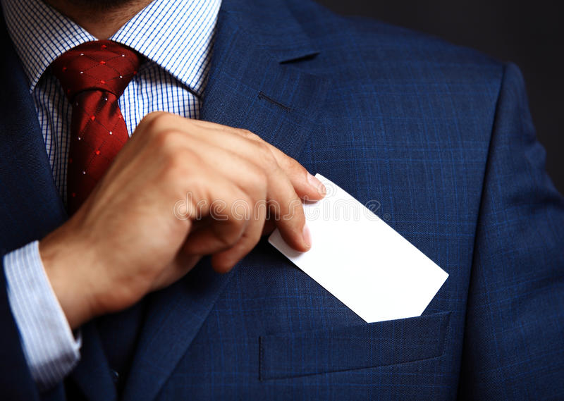 Businessman putting visit card in the pocket royalty free stock photo
