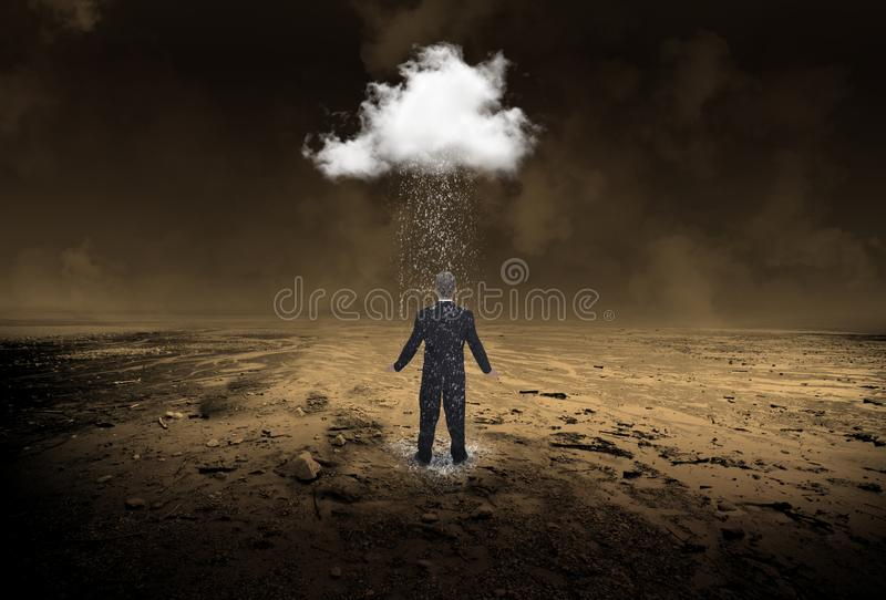 Businessman, Rain, Business, Sales, Marketing. Surreal scene of a businessman in a desolate desert with a single rain storm cloud. Abstract concept for weather stock photo