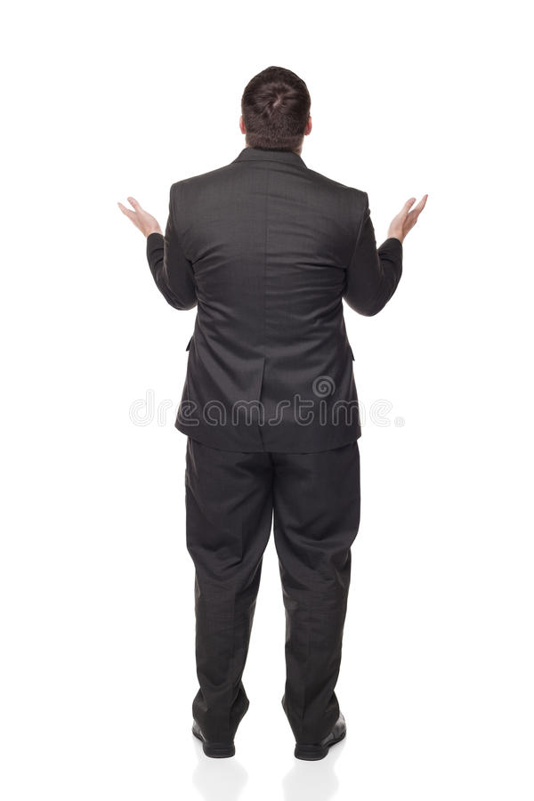 Businessman raising arms in disbelief. Isolated full length studio shot of the rear view of an upset businessman raising his arms in disbelief as if giving up royalty free stock photography