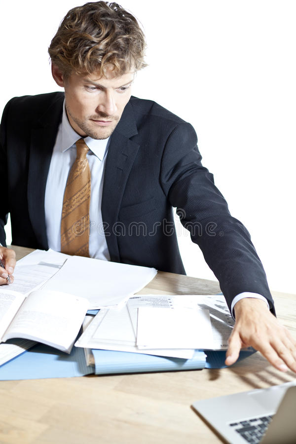 Businessman reaching for laptop at work stock photos