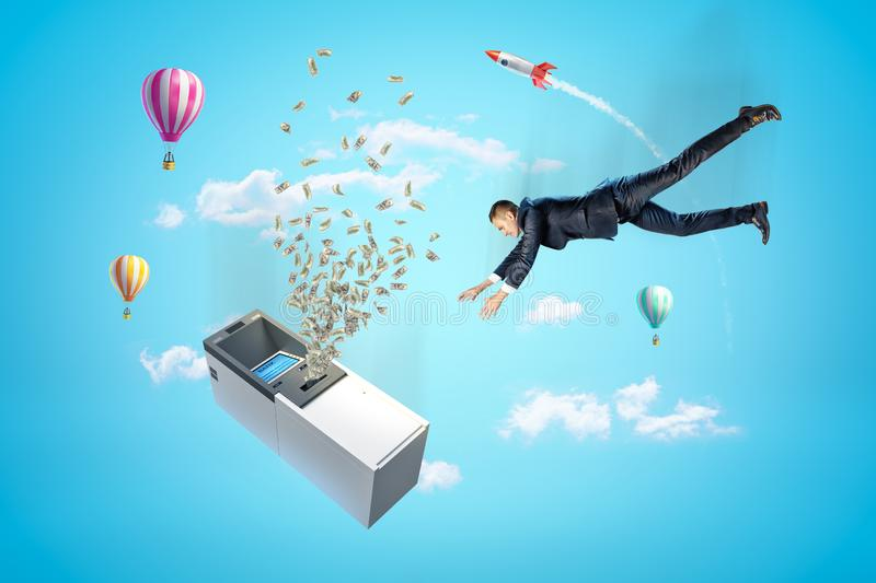 Businessman reaching to ATM machine with dollars flying out, hot air balloons and silver red space rocket in the air on. Blue background. People and objects stock photos