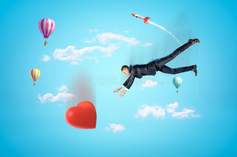 Businessman reaching to big red heart with hot air balloons and silver red space rocket in the air on blue background. Concept art. People and objects stock photos