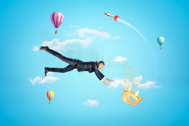 Businessman reaching to golden crown with hot air balloons and silver red space rocket in the air on blue background stock images