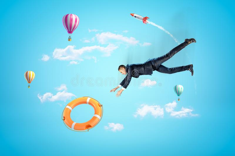 Businessman reaching to orange boat lifebuoy with hot air balloons and silver red space rocket in the air on blue. Background. People and objects. Risk and stock photography