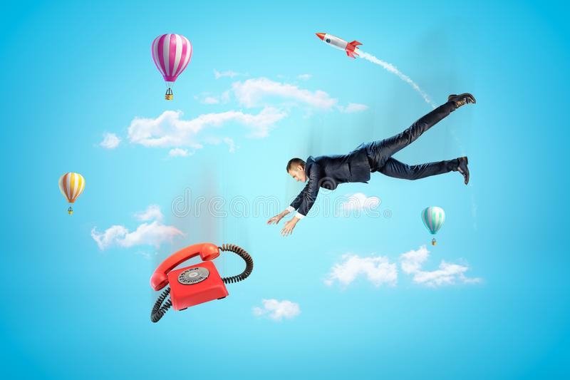 Businessman reaching to red retro telephone with hot air balloons and silver red space rocket in the air on blue stock photography