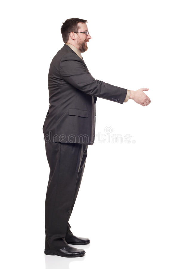 Businessman reaching to shake hands. Isolated full length studio shot of the side view of a businessman reaching out to shake hands royalty free stock photography