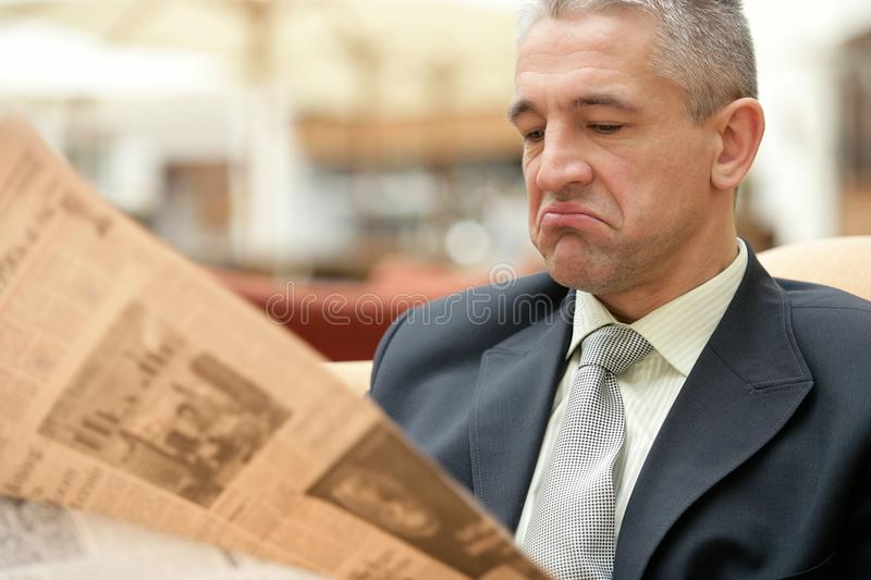 Businessman reading bad news on a business newspaper. Gray haired senior businessman reading bad news on a business newspaper stock image