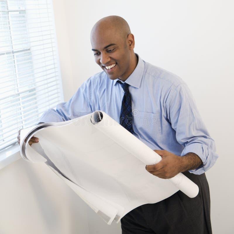 Businessman reading blueprint.