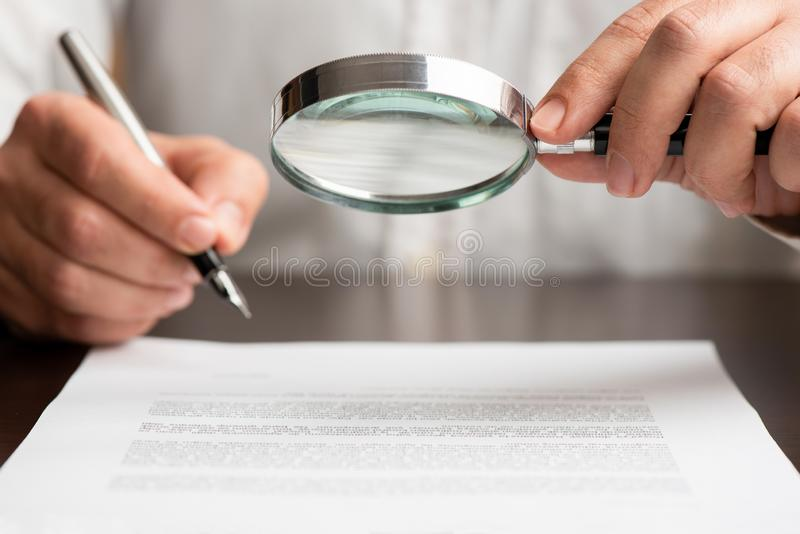 Businessman Reading Contract Carefully Using Magnifying Glass royalty free stock photo