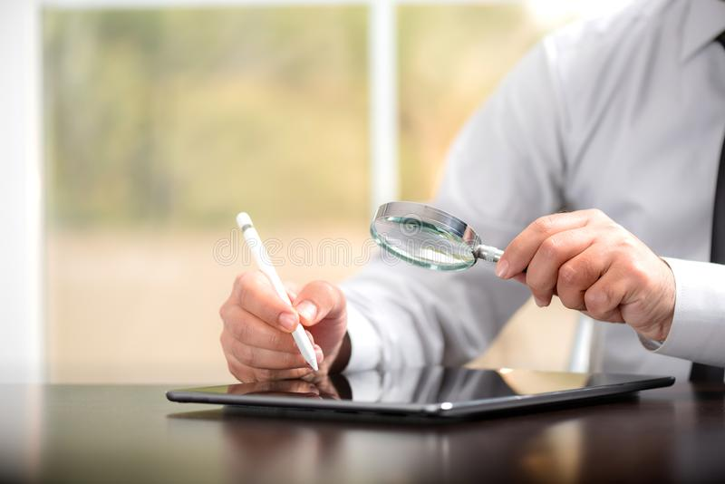 Businessman Reading Contract Details Before Signing Digital Using Tablet And Stylus royalty free stock photos