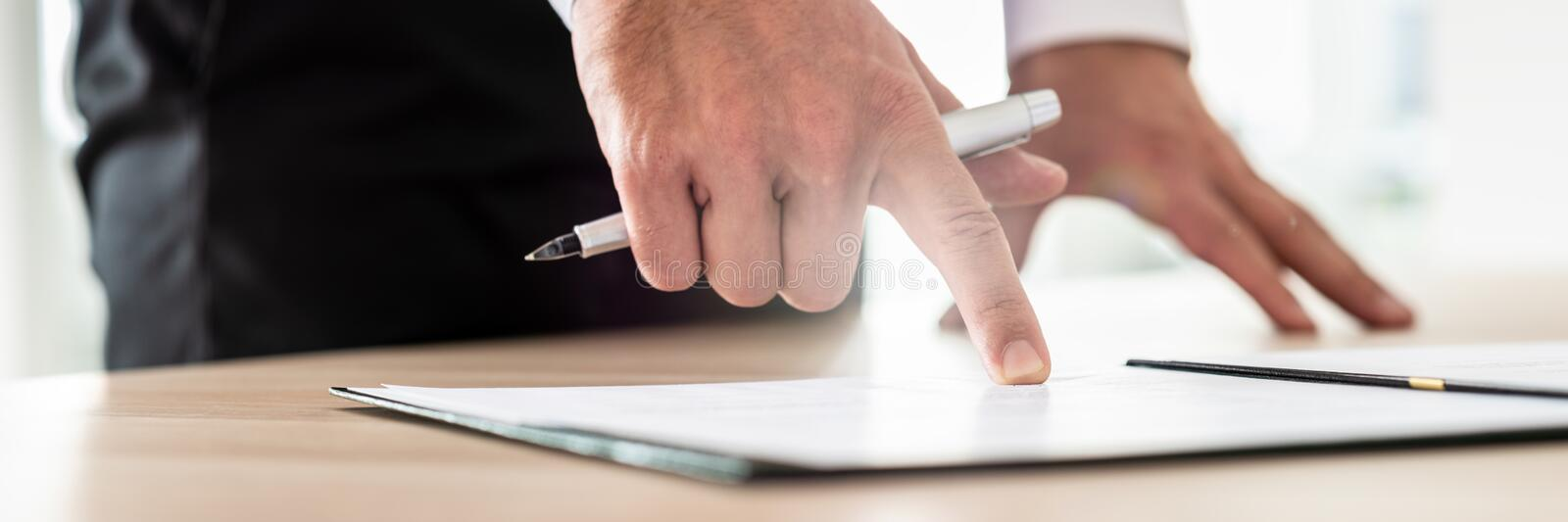 Businessman reading contract or document in folder pointing with royalty free stock photo