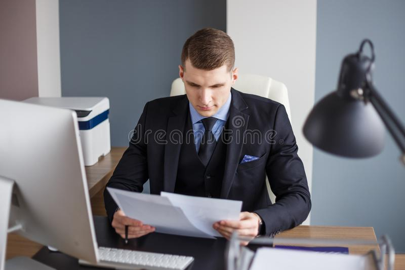 Businessman reading contract in office royalty free stock images