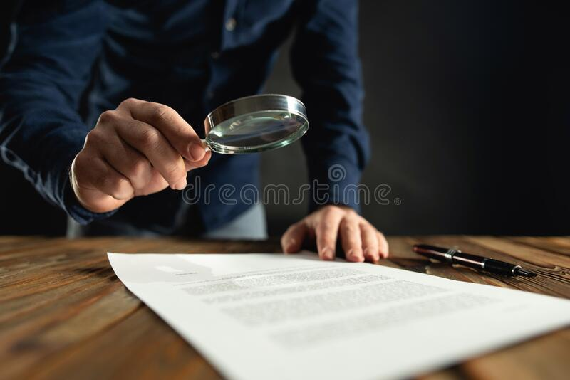 Businessman Reading Contract Using Magnifier Before Signing stock image