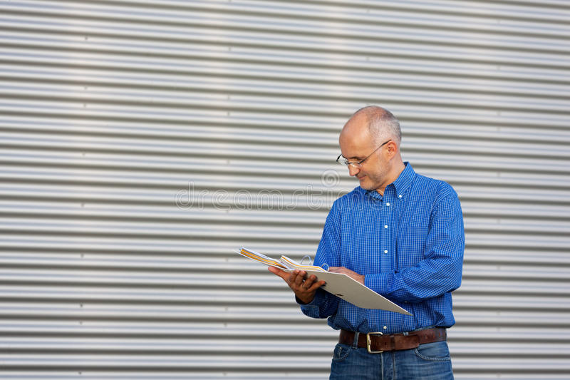 Businessman Reading Documents In Binder Against Shutter royalty free stock images