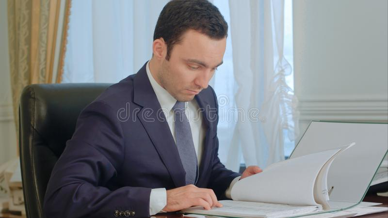 Businessman reading documents and talking on landline phone royalty free stock photo