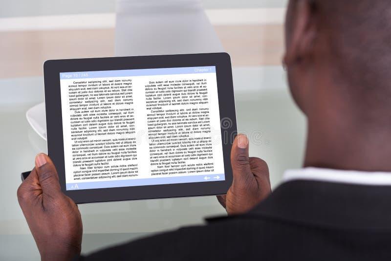 Businessman reading e-book stock photo