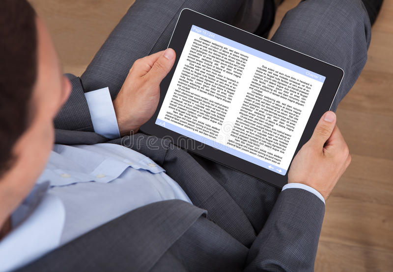 Businessman reading ebook in office. Midsection of businessman reading eBook in office royalty free stock photography