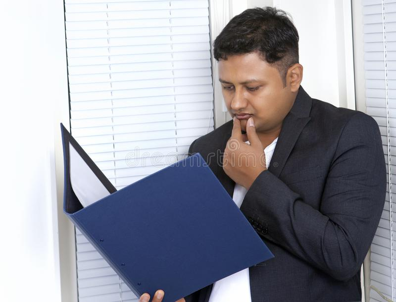 Businessman reading file, busy expression royalty free stock images