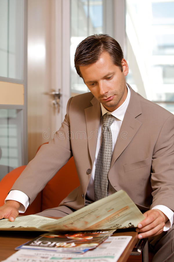 Businessman reading newspaper stock photos