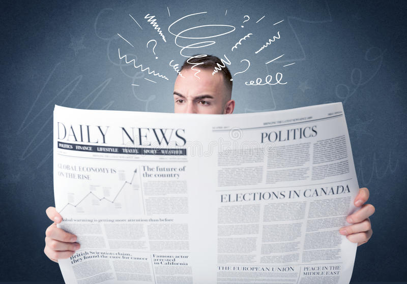 Businessman reading newspaper. Confused businessman holding big newspaper royalty free stock photo