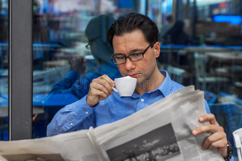 Businessman reading a newspaper while drinking coffee. Businessman Working Reading Newspaper Information Concept.  stock photo