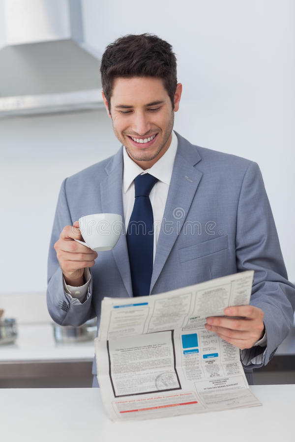 Businessman reading a newspaper and drinking a coffee royalty free stock photo