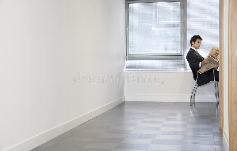 Businessman Reading Newspaper In Empty Room stock photos