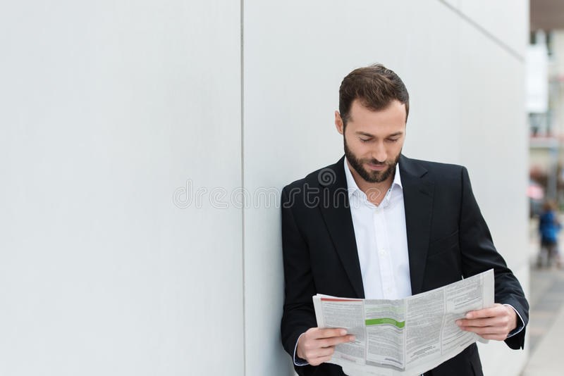 Businessman reading a newspaper on his lunch break stock photos