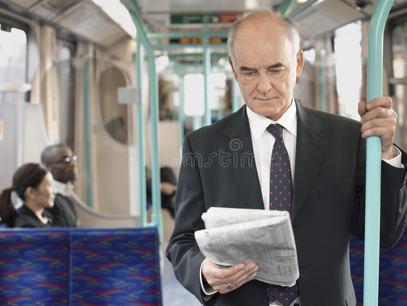 Businessman Reading Newspaper In Train. Mature businessman reading newspaper in the train with commuters sitting in background stock photography