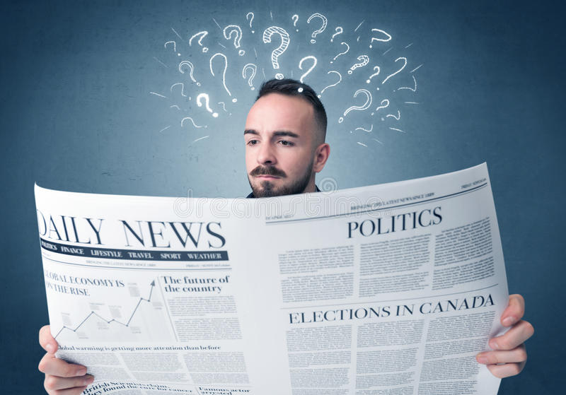 Businessman reading newspaper. Young confused businessman reading daily newspaper with question marks above his head stock photo
