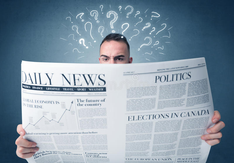 Businessman reading newspaper. Young confused businessman reading daily newspaper with question marks above his head stock image