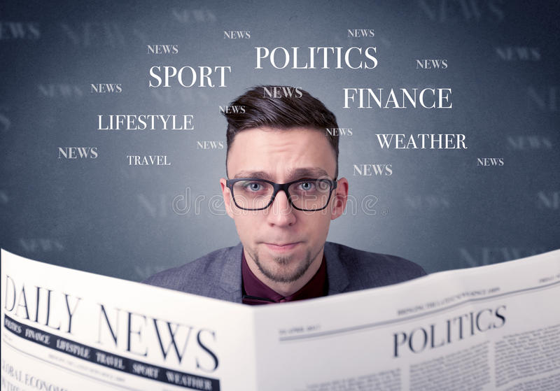 Businessman reading newspaper. Young smart businessman reading daily newspaper royalty free stock images