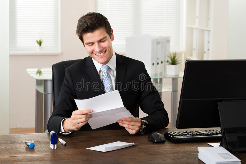 Businessman Reading Paper In Office stock image