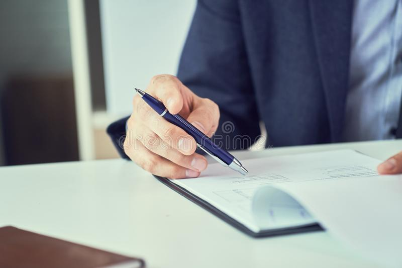 Businessman reading rental contract before making a deal. Corporate man with pen in hand working in modern office royalty free stock photos
