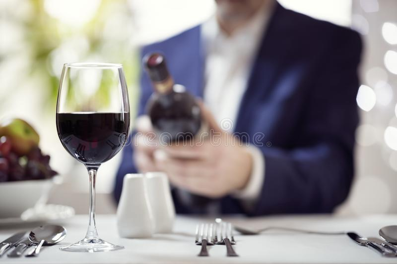 Businessman reading a wine bottle label in restaurant royalty free stock photo